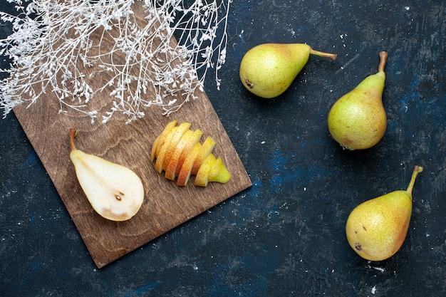 Draufsicht auf frische birnen, ganz geschnitten und süß auf dunkelblauem schreibtisch, fruchtfrisches, mildes essen