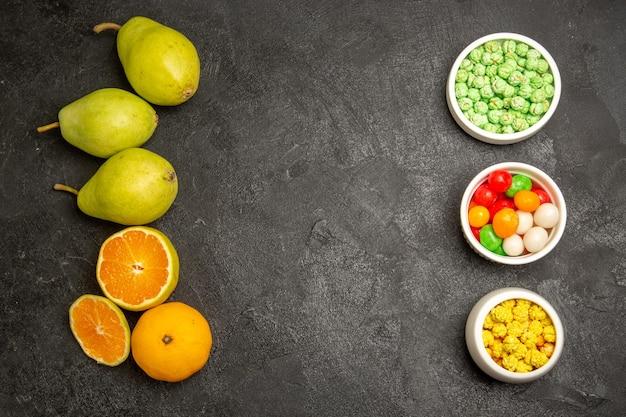 Draufsicht auf frische birnen mit mandarinen und bonbons auf dunkelgrau