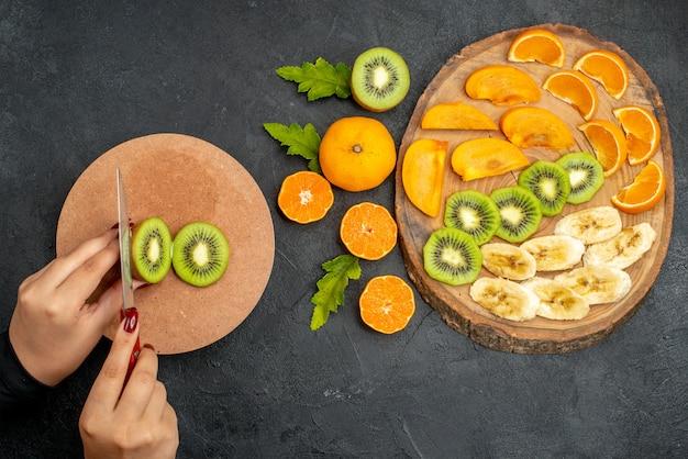 Draufsicht auf frische früchte auf einem holztablett und kiwis von hand auf schneidebrett auf schwarzer oberfläche hacken
