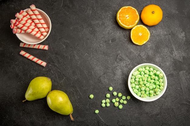 Draufsicht auf frische früchte mit bonbons auf dunkelgrau