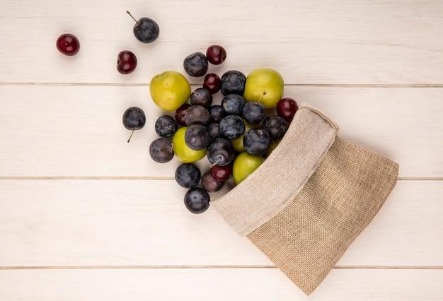 Draufsicht auf frische früchte wie grüne kirschpflaumenkirschen und schlehen, die aus einem leinensack auf einem weißen hölzernen hintergrund fallen