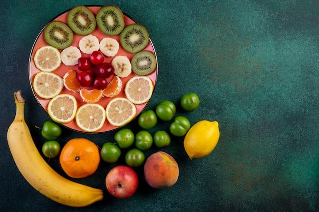Draufsicht auf frische früchte zitronen-mandarinen-bananen-pfirsich-apfelgrün-sauerkirsch-pflaumen und geschnittene früchte mit roten kirschen auf platte auf dunkelheit