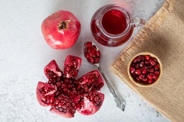 Draufsicht auf frische granatäpfel. ganze oder geschnittene granatäpfel auf grauer oberfläche.