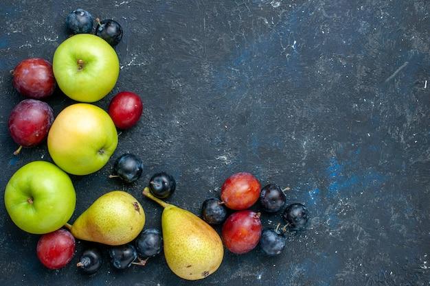 Draufsicht auf frische grüne äpfel mit birnenschwarzdorn und pflaumen auf dunkelblauem, frischem, mildem essen mit fruchtbeeren