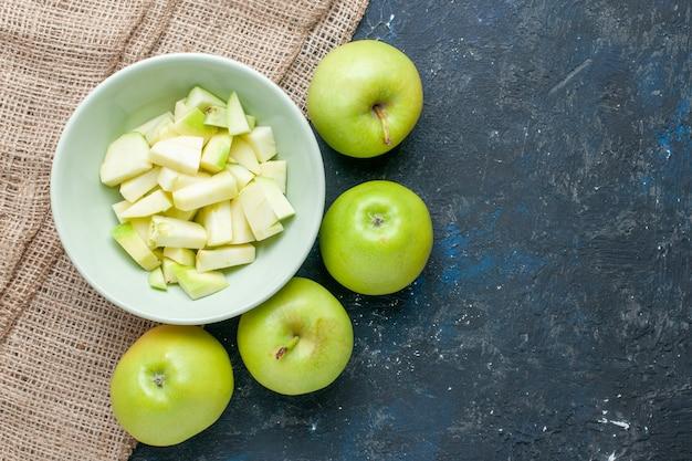 Draufsicht auf frische grüne äpfel weich und saftig mit geschnittenem apfel innerhalb platte auf dunkelblauem schreibtisch, fruchtfrischnahrungsmittelgesundheitsvitamin