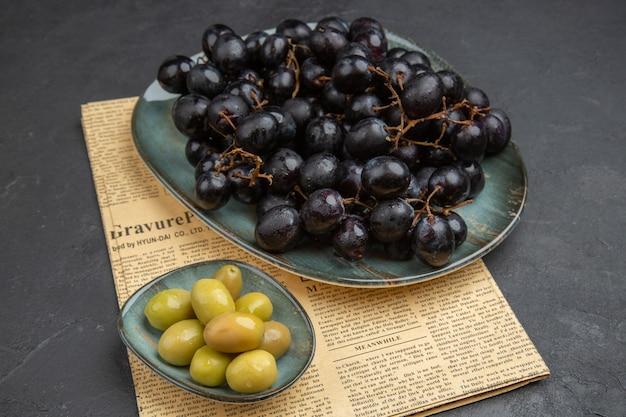 Draufsicht auf frische grüne bio-oliven und bündel schwarzer trauben auf einer alten zeitung auf dunklem hintergrund