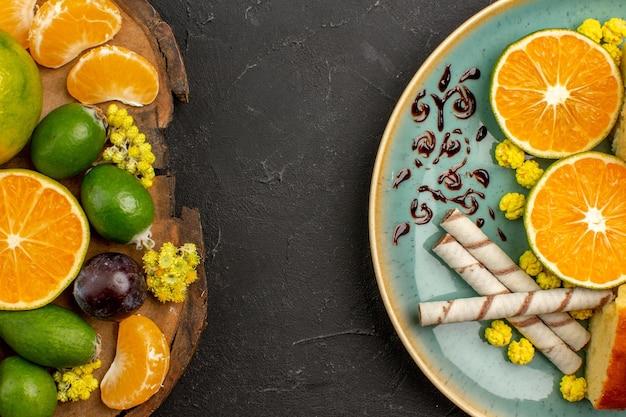 Draufsicht auf frische grüne mandarinen mit feijoas und kuchenscheiben auf dunkelheit on