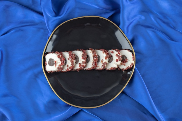 Draufsicht auf frische hausgemachte kekse in scheiben auf schwarzem teller über blauem tisch.