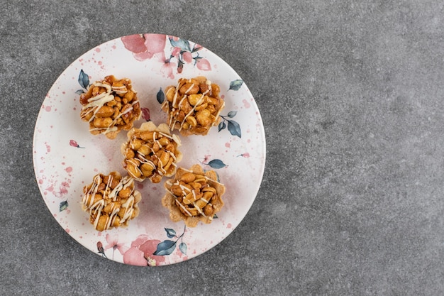 Draufsicht auf frische hausgemachte kekse mit erdnuss auf teller über grauer oberfläche