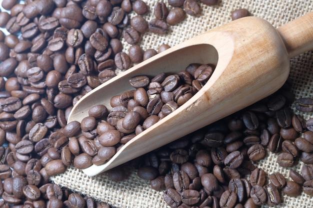 Draufsicht auf frische kaffeebohnen und löffel auf tisch.