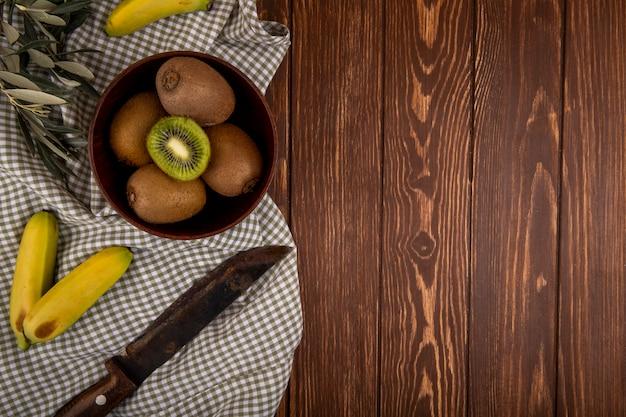 Draufsicht auf frische kiwis in einer holzschale und frischen bananen mit altem küchenmesser auf rustikalem mit kopienraum