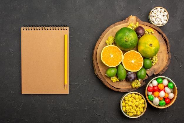 Draufsicht auf frische mandarinen mit feijoa und bonbons auf schwarz Kostenlose Fotos