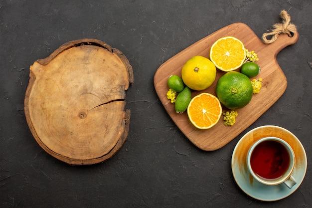 Draufsicht auf frische mandarinen mit feijoa und tasse tee auf schwarz