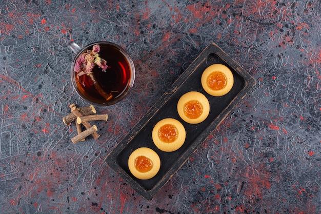 Draufsicht auf frische marmeladenplätzchen mit duftendem tee auf rustikalem.