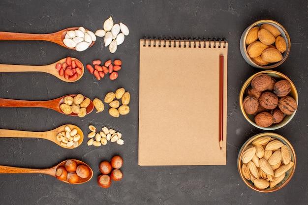 Draufsicht auf frische nüsse, erdnüsse und andere nüsse auf dunkler oberfläche