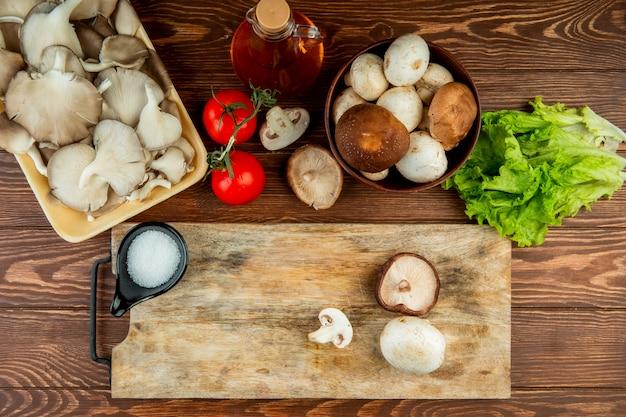 Draufsicht auf frische pilze in schüssel und tomaten mit salat und einem holzbrett mit salz und geschnittenen pilzen auf holz rustikal