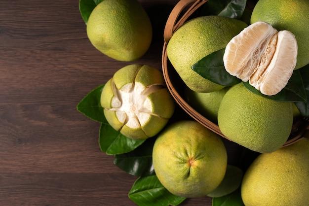 Draufsicht auf frische pomelo auf dunklem holztischhintergrund für mid-autumn festival-frucht.