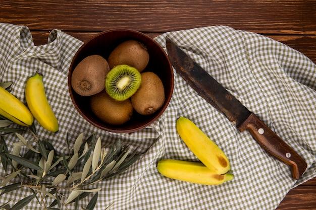 Draufsicht auf frische reife kiwis in einer holzschale und frischen bananen mit altem küchenmesser auf rustikalem