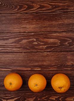 Draufsicht auf frische reife orangen, die in einer reihe auf holz mit kopierraum ausgekleidet sind