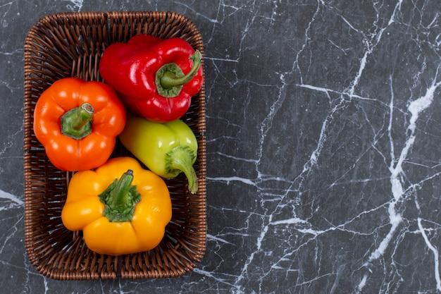 Draufsicht auf frische reife paprika im geflochtenen korb.