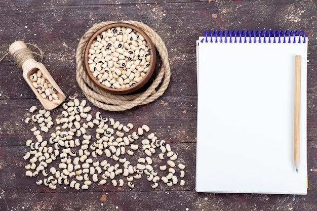 Draufsicht auf frische rohe bohnen, die über das ganze braun verteilt sind, mit notizblocknahrung rohen bohnenharicot
