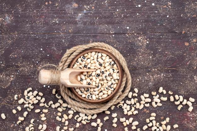 Draufsicht auf frische rohe bohnen in der braunen schüssel und verteilt auf der ganzen braunen haricot der rohen bohnen des lebensmittels