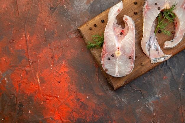 Draufsicht auf frische rohe fische und pfeffer auf holzschneidebrett auf der linken seite auf mischfarboberfläche
