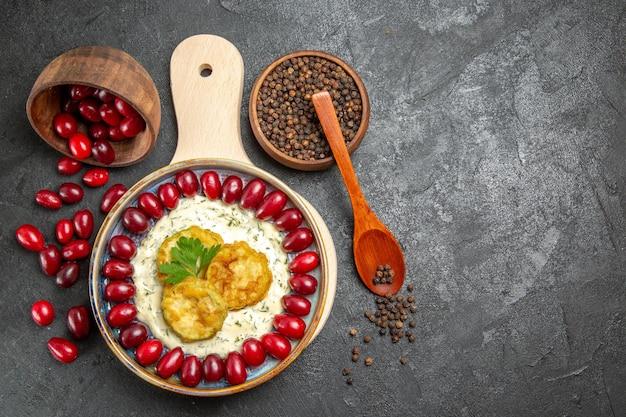Draufsicht auf frische rote hartriegel mit gewürzen und gekochten kürbissen auf grauer oberfläche