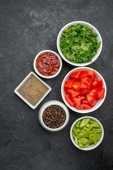 Draufsicht auf frische rote tomaten in scheiben geschnittenes gemüse mit grüns auf schwarz