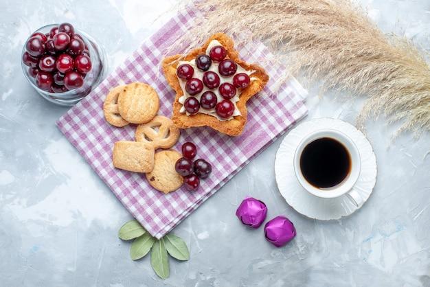 Draufsicht auf frische sauerkirschen in teller mit sternförmigem cremigem kuchentee und keksen auf weißem schreibtisch, fruchtsauerkuchen-keks