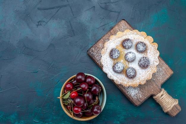 Draufsicht auf frische sauerkirschen mit rundem kuchen auf dunklem schreibtisch, obstkuchen-kekszuckersüß