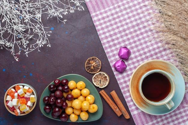 Draufsicht auf frische süßkirschen in teller mit teezimt und bonbons auf der dunklen oberfläche