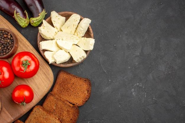 Draufsicht auf frische tomaten mit dunkelheit. brotlaibe und weißkäse auf schwarz