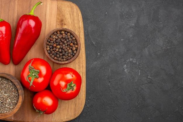 Draufsicht auf frische tomaten mit gewürzen und pfeffer auf schwarz
