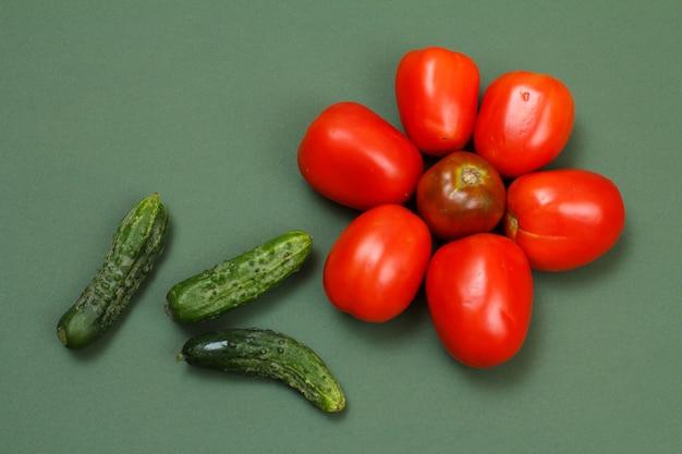 Draufsicht auf frische tomaten und gurken auf grünem hintergrund. gemüse auf küchentisch. ansicht von oben.