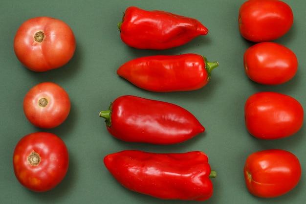 Draufsicht auf frische tomaten und paprika auf grünem hintergrund. gemüse auf küchentisch. ansicht von oben.
