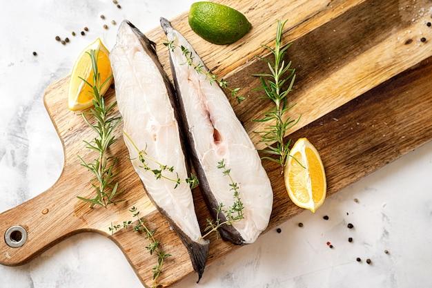 Draufsicht auf frische und rohe heilbutt-fischsteaks mit kräutern und zitrone auf holzbrett. omega-3-fette sind gut für geistige klarheit. gehirnnahrung
