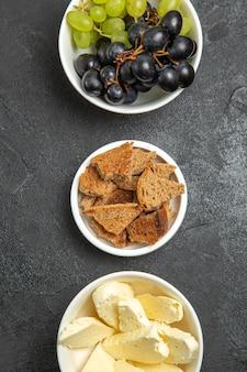 Draufsicht auf frische, weiche trauben mit brot und käse auf dunkler oberfläche