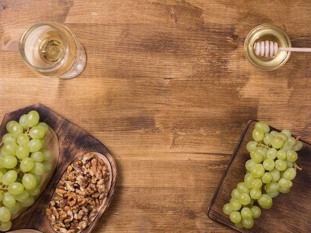 Draufsicht auf frische wollnüsse, serviert mit trauben und honig. rustikaler tisch. glas weißwein. kopieren sie platz zur verfügung.