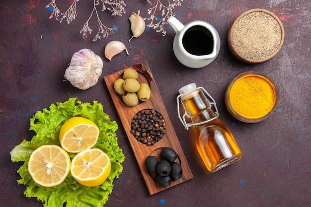 Draufsicht auf frische zitronenscheiben mit grünem salat und oliven auf dunkel