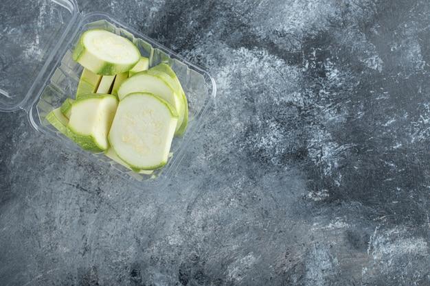 Draufsicht auf frische zucchinistücke im plastikbehälter.