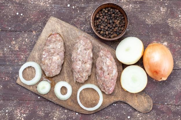 Draufsicht auf frische zwiebeln ganz und geschnitten mit rohen fleischkoteletts auf braunem, pflanzlichem lebensmittelzutatprodukt