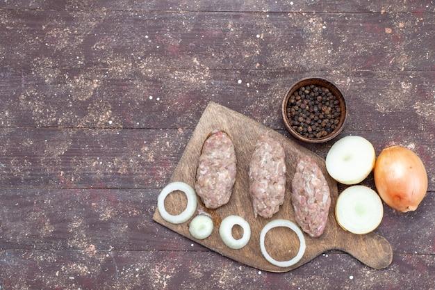 Draufsicht auf frische zwiebeln ganz und in scheiben geschnitten mit rohen fleischkoteletts auf braunem, pflanzlichem lebensmittelbestandteilprodukt fleischmehl