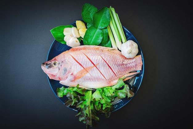 Draufsicht auf frischen fisch und gemüse in keramikgeschirr auf dem dunklen tisch, der zum kochen vorbereitet ist.