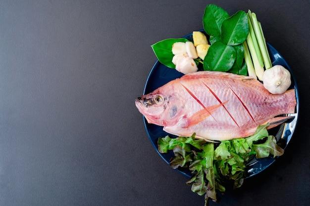 Draufsicht auf frischen fisch und gemüse in keramikgeschirr, das zum kochen zubereitet wird