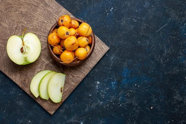 Draufsicht auf frischen grünen apfel, halb geschnitten, geschnitten mit süßkirschen auf dunklem, fruchtfrischem, weichem, reifem