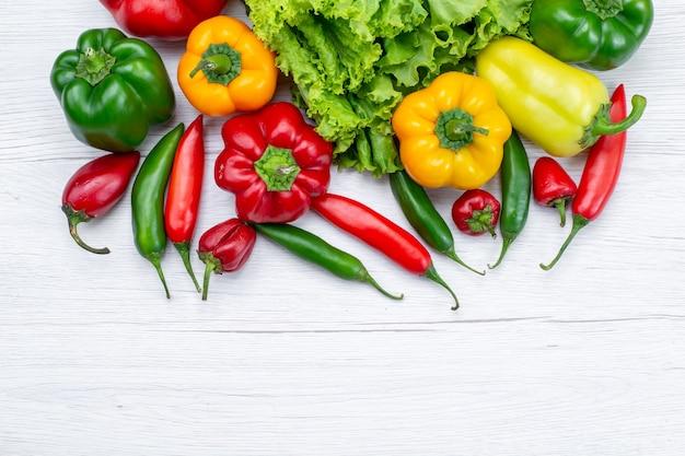 Draufsicht auf frischen grünen salat zusammen mit paprika und würzigen paprikaschoten auf leichtem schreibtisch, zutat für gemüsemahlzeiten
