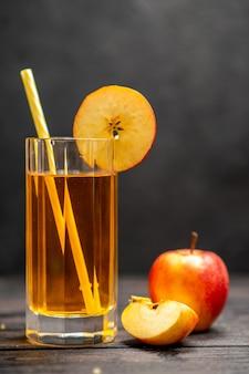 Draufsicht auf frischen natürlichen köstlichen saft in zwei gläsern mit roten apfellimetten auf schwarzem hintergrund