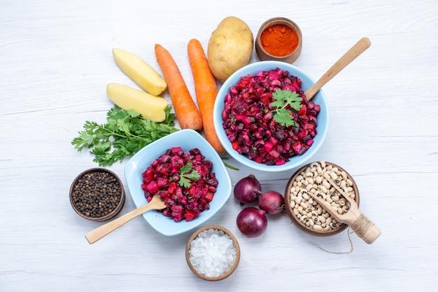 Draufsicht auf frischen rübensalat mit geschnittenem gemüse in blauen tellern mit zutaten auf hellem schreibtisch, gemüsesalat lebensmittel mahlzeit gesundheitssnack