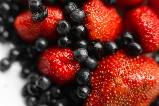Draufsicht auf frisches buntes sortiment der beeren, erdbeeren und schwarze johannisbeeren auf weißem teller. gesundes ernährungskonzept